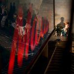 """Geschichten aus dem Wiener Wald, eine Spiegelung des Maxim-Logos. Szenenfoto aus """"Geschichten aus dem Wiener Wald"""" von Horvath auf der Wasserburg Dessau-Roßlau im Sommertheater, in der Regie von Andrea Pinkowski, Fotos © Jenny Fitz, die Schauspielerinnen Jacob Meinecke und Mora Thurow."""